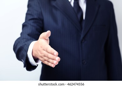 Businessman gesturing with his hand on grey background