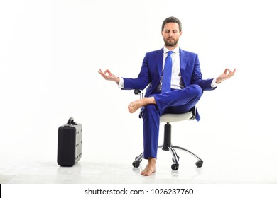 Businessman gets rid of stress and relaxing after hard working day. Man in suit or businessman sit on office chair and meditate or practice yoga, isolated on white background. Work and relax concept.