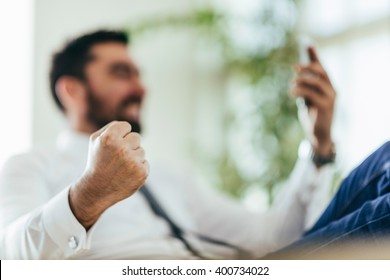 Businessman getting good news over smart phone, fist pumping. Selective focus on fist