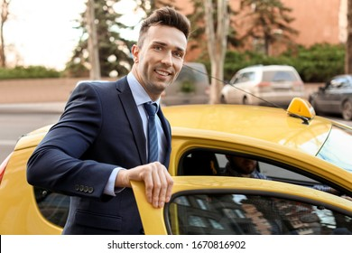Businessman getting in taxi on city street