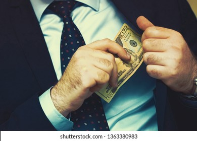 Businessman gives a bribe to an employee in the office. Concept - corruption. Giving a bribe. Money in hand. The concept of corruption and bribery. Toning