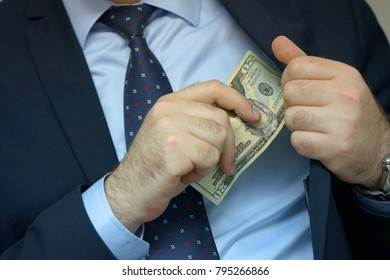 A businessman gives a bribe to an employee in the office. Concept - corruption. Giving a bribe. Money in hand. The concept of corruption and bribery