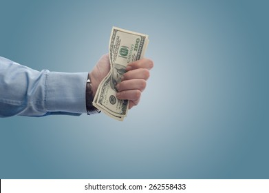 Businessman giving away a fistful of dollars with copy space