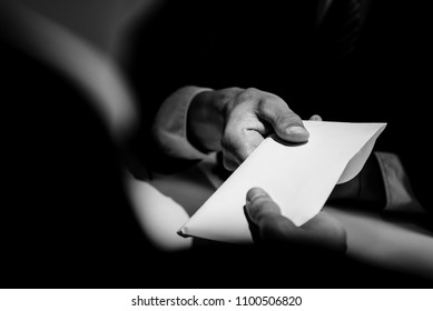 Businessman giving bribe money in the  envelope to partner in a corruption scam with black and white tone