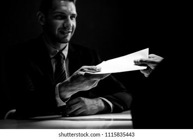 Businessman giving bribe money in the envelope to partner in a corruption scam, black and white tone