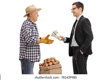 Businessman giving bundles of money to a farmer with a burlap sack filled with potatoes isolated on white background
