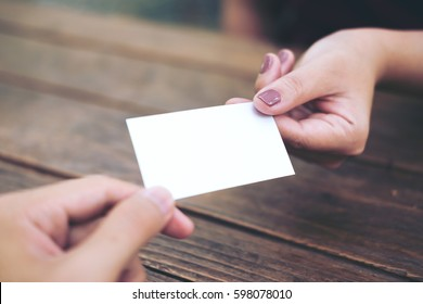 Businessman giving  business card to businesswoman with wooden table background