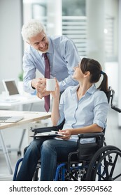 Businessman giving a cup of coffee to her disabled female colleague during a break at office, assistance and friendship concept