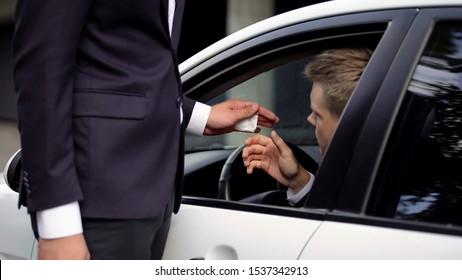 Businessman giving drug plastic bag to car driver, illegal narcotic trafficking