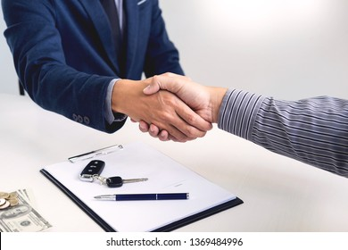 Businessman giving end key to customer after good deal agreement. while loan agreement being approved and calculator, Buy house concept
