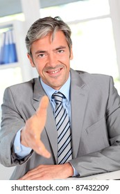 Businessman giving handshake to client