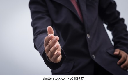 Businessman giving a helping hand,asking or offering help in a business suit