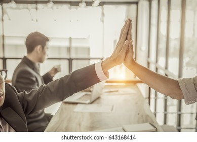 businessman giving hi five/ touching hands and thumb up during meeting for celebration business achievement and success with teamwork