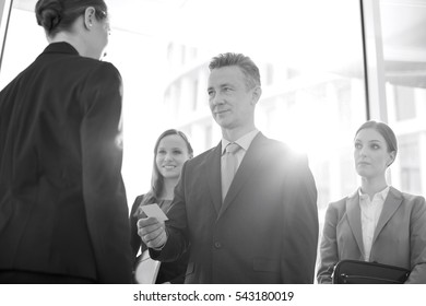 Businessman giving his card to female coworker in office