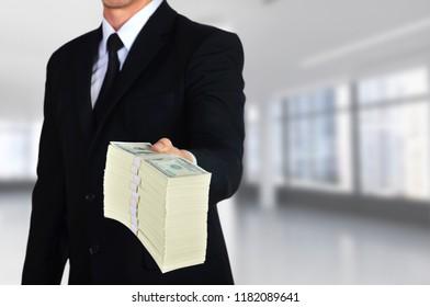 businessman giving huge stack of one hundred dollar bills