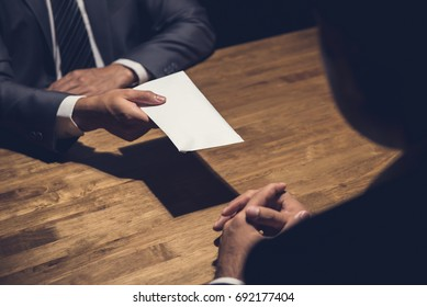 Businessman giving money in the envelope to his partner in the dark - bribery and venality concept