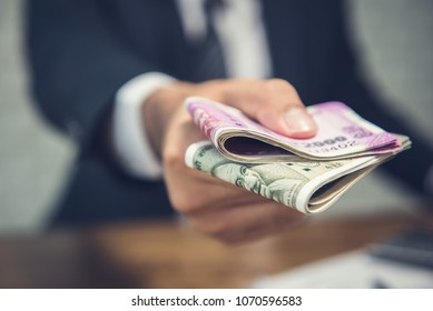 Businessman giving money in the form of Indian Rupees currency for services rendered