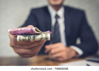 A businessman giving money in the form of Indian Rupees for services rendered as per a signed contract.