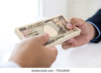 Businessman giving money in the form of Japanese Yen currency to his partner for service rendered - financial, loan and cash payment concepts