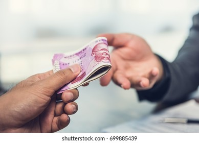 Businessman giving money, Indian rupee currency, to hs partner - payment, loan and bribery concept