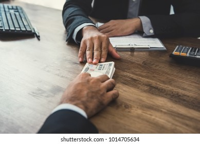 Businessman giving money, Japanese yen banknotes, to his partner at the table while making contract - loan, bribery and corruption concepts