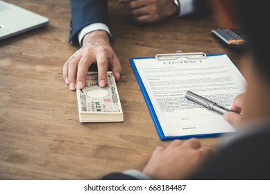 Businessman giving money, Japanese yen banknotes, to his partner while making contract - loan, bribery and corruption concepts