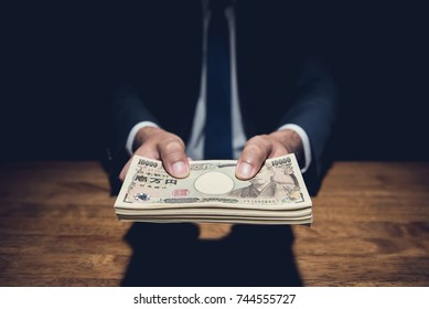 Businessman giving money, Japanese yen currency, at the table in dark private room -  financial, bribery and corruption concepts
