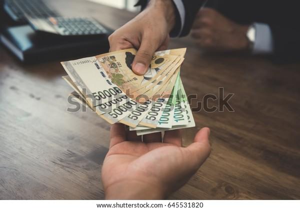 Businessman giving money, Korean won banknotes, to his partner - bribery concepts