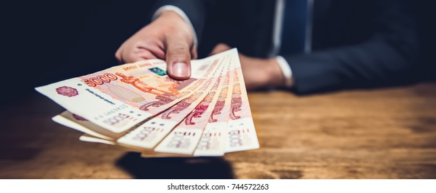 Businessman giving money, Russian Ruble currency, at the table in dark private room, loan, bribery and corruption concepts - panoramic banner
