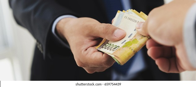 Businessman giving money, South Korean won banknotes, to his partner, bribery concept - panoramic banner