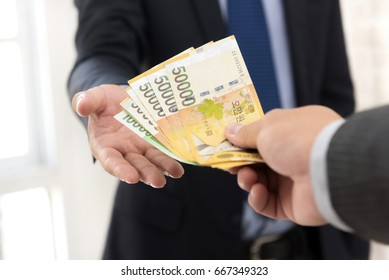 Businessman giving money, South Korean won banknotes, to his partner
