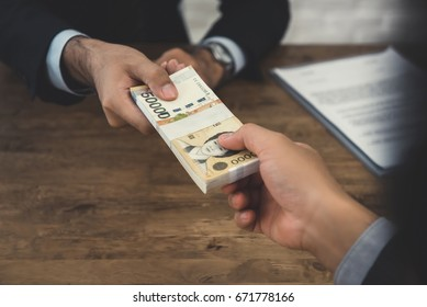 Businessman giving money, South Korean won banknotes, to his partner at the desk