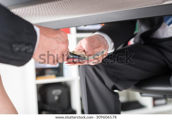 Empresario dando dinero debajo de una mesa