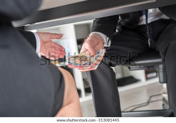 Geschäftsmann, der unter Tisch Geld spendet
