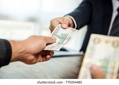 Businessman giving money, United Arab Emirates dirham currency, to his partner
