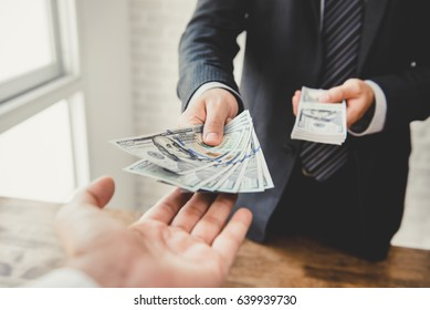Businessman giving money, US dollar bills - loan,payment, bribery and corruption concepts