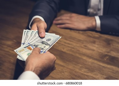 Businessman giving money, US dollar (USD) bills, to his partner on the table in the dark - bribery, corruption and venality concepts