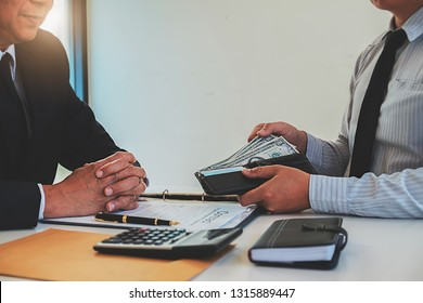 Businessman giving money while making deal to agreement a real estate contract and financial corporate.Bribery and corruption concept
