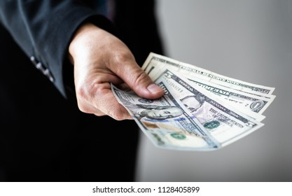 Businessman giving (or paying) money, US dollar bills - bribery, loan and financial concepts, Selective focus