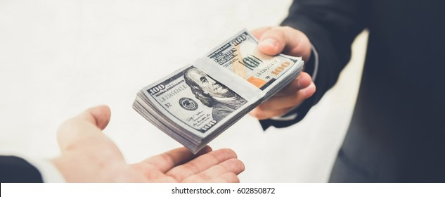 Businessman giving (or paying) money to a man, US dollar bills - bribery, loan and financial concepts, panoramic banner