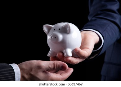 Businessman giving a piggy bank to you (isolated on black)
