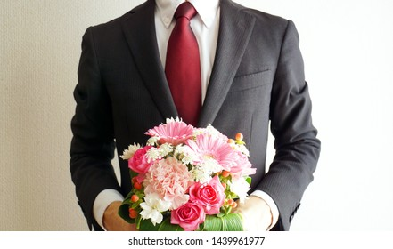 Businessman giving a pink bouquet.