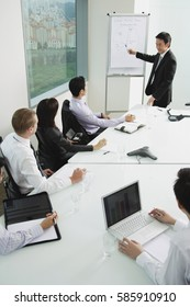 Businessman giving presentation, pointing at whiteboard
