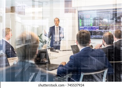 Businessman giving a talk in conference room. Business executive delivering presentation to business partners during business meeting. Corporate business concept.