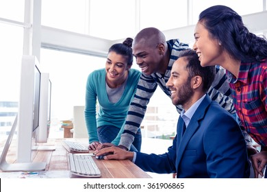 Businessman giving training to team over computer in creative office
