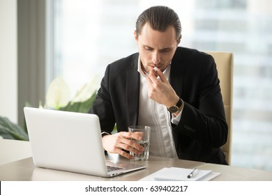 Businessman with glass of water takes white round pill at work desk in office. Office worker drinking medicines at workplace. Young entrepreneur swallows painkiller, sedatives for efficiency recovery