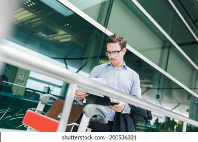 Businessman in glasses reading a customs declaration at the airport