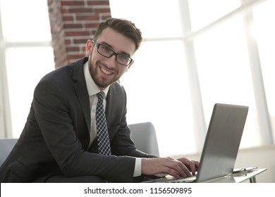 businessman with glasses is sitting at the desk in the office