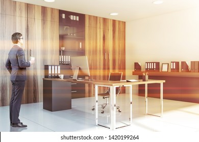 Businessman in glasses standing in CEO office with white walls and floor, wooden computer table, shelves with folders and bookcase. Toned image