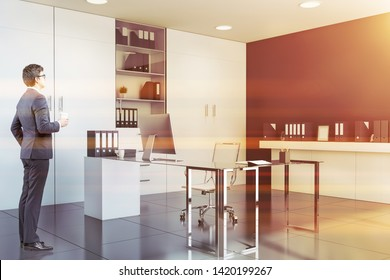 Businessman in glasses standing in CEO office with black walls, white bookcase and glass computer table. Concept of manager lifestyle. Toned image